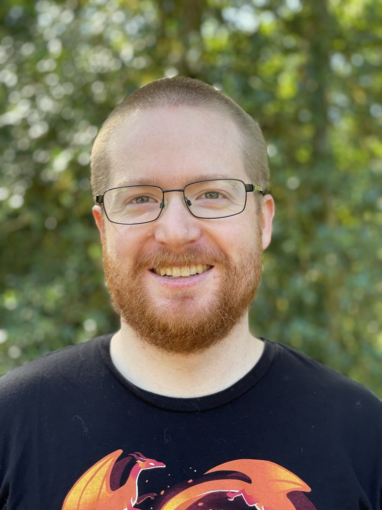 Headshot of Jake smiling in front of a green background.  Jake has buzzed hair, a red beard, hazel eyes, pale skin, and thin framed black glasses.